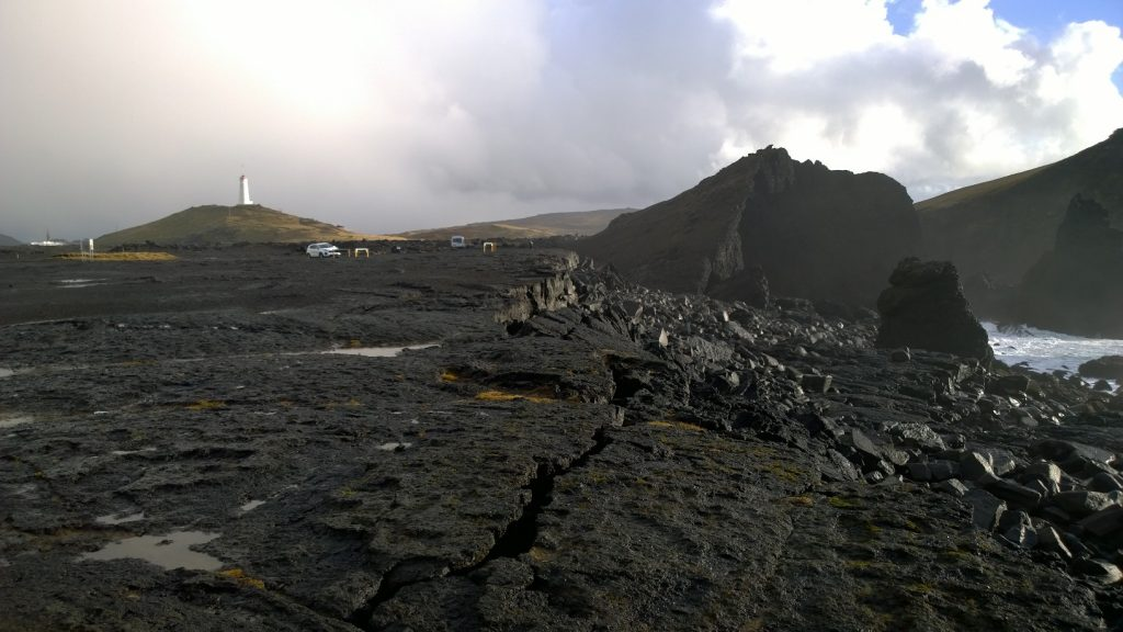 View from the Reykjanes shore. Drill rig Þór seen in the background to the left of the lighthouse, located on the IDDP-2 well.